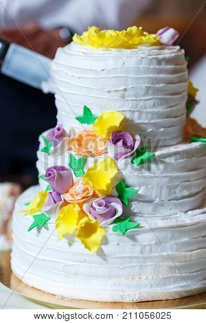 Groom in suit and bride in white dress cut beautiful multi level wedding cake decorated with cream yellow flowers greenery and gold. Delicious dessert at wedding banquet