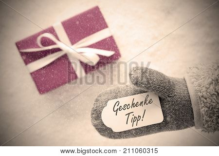 Glove With Label With German Text Geschenk Idee Means Gift Idea. Pink Or Rose Gift Or Present On Snow In Background. Seasonal Greeting Card With Snowflakes And Instagram Filter