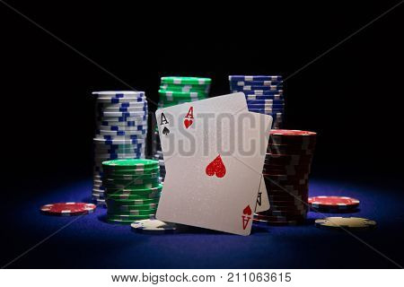 Pair of aces and poker chip on black background