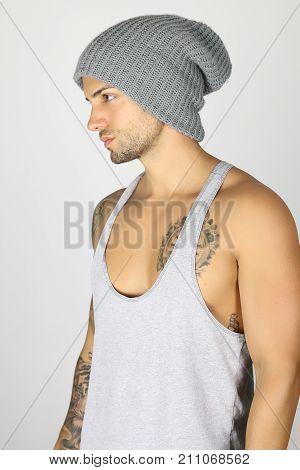 Handsome fashion man posing in studio in hat . Sexy male wearing a tank top in studio