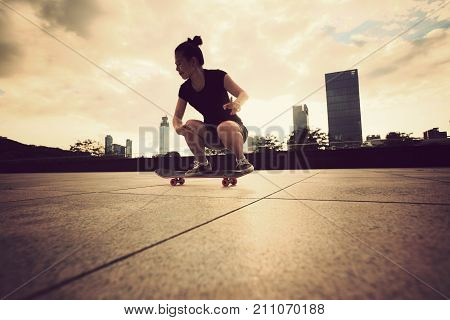 young woman skateboarder skateboarding at sunrise city