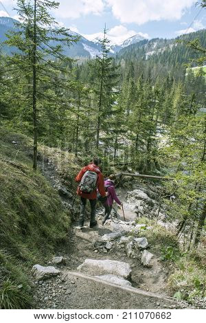 Two wanderers on a trail. Summer mountains landscape. Adventure
