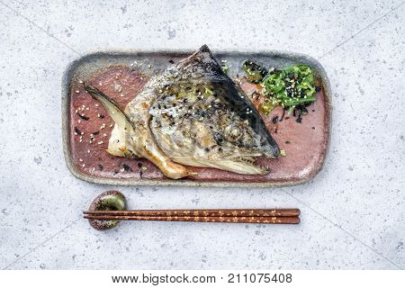 Traditional barbecue Japanese Kama Yaki broiled salmon fish head with wakame lettuce as close-up on a plate
