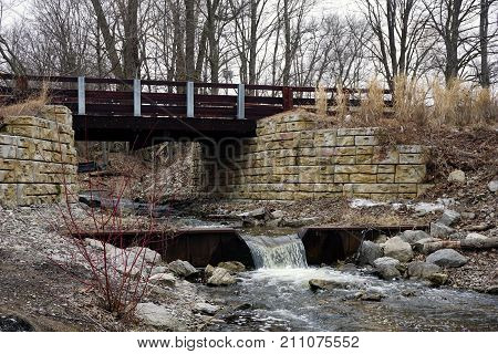 A bridge, along the Little Traverse Wheelway, which connects Charlevoix, Petoskey and Harbor Springs, Michigan, allows hikers and bicyclists to cross Tannery Creek. poster