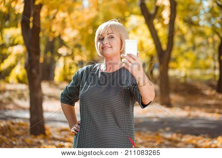 Close-up of a beautiful, smiling and adult woman with blonde hair and with a gadget on a blurred autumn park background. Pretty middle-aged woman makes a selfie outdoor.