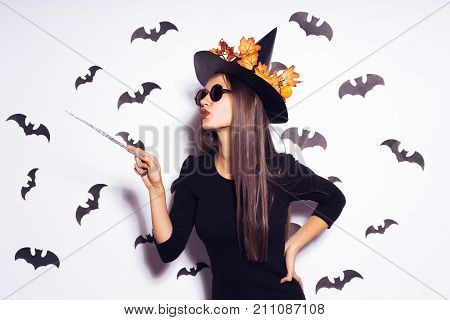 a young, gothic, sexy gothic girl celebrates halloween, in the image of a witch, wearing sunglasses, holding a magic wand