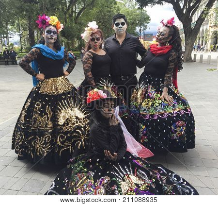 XALAPA, VERACRUZ, MEXICO- NOVEMBER 26, 2017: Man painted as a skull and women dressed as traditional catrinas posing at the street in Xalapa, Veracruz, Mexico