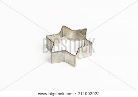Star shaped Christmas cookie cutter over white. Tin biscuit cutter, a tool to cut cookie dough in particular shape and to make cutouts. Hexagram shaped and six pointed geometric star figure. Photo.