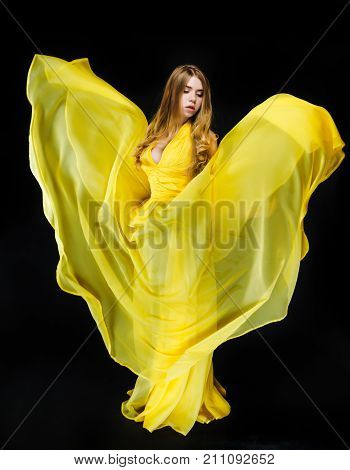 Natural beauty. Portrait of a beautiful young woman in a yellow dress with a shiny blonde straight long hair, Blue eyes close up portrait studio on black.