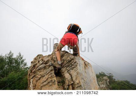 successful woman climber climbing rock on the top of mountain