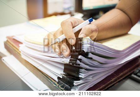Businessman hands searching nfinished documents stacks of paper files on office desk for report papers piles of unfinish papers sheet achieves with clips indoor Document is written drawnpresented.