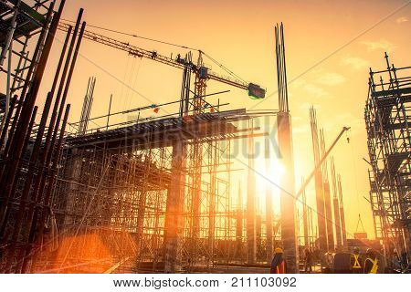Industrial machinery and the construction crane. Cranes and skyscraper under construction, city skyline at sunset, sunrise Building under Construction site