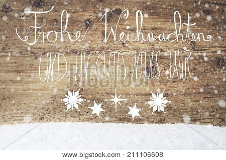 White German Calligraphy Frohe Weihnachten Und Ein Gutes Neues Jahr Means Merry Christmas And Happy New Year. Rustic Wooden Background With Snow And Snowflakes