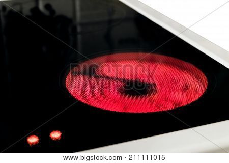 Induction cooker with control hot temperature indicators. Electric hob close-up with ceramic surface. Stove top panel. Selective focus.