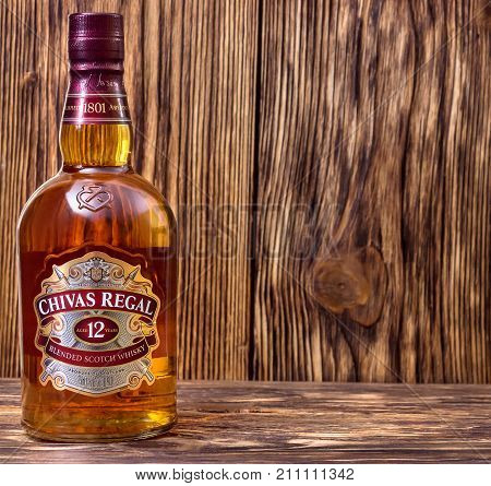 Ternopil Ukraine - August 26 2017: Bottle of Blended scotch whisky Chivas Regal. 12 years old scotch whiskey. Made in Scotland. Bottle of whisky on wooden background.