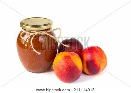 Jam pot on white background with ripe appetizing peaches