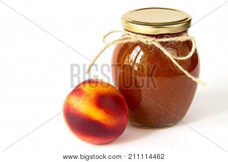 Fruit jam jar. Nectarine jam in a glass jar and fresh peaches on white background