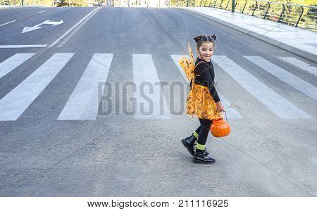Little girl at zebra crossing in halloween costumes. She is walking towards children party site. Badajoz Spain