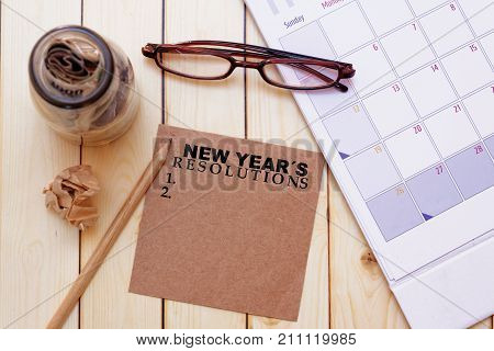 New year's resolutions concept with eye glassescalendar pencilcrumpled paper and a glass jar full of money on wooden background