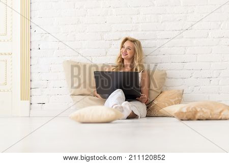 Young Blonde Woman Sit On Floor On Pillows Using Laptop Computer, Beautiful Girl Happy Smiling Over White Brick Wall Look Up To Copy Space