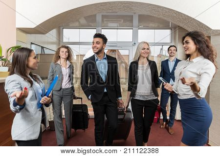 Hotel Receptionist Meeting Business People Group In Lobby, Guests Arrive