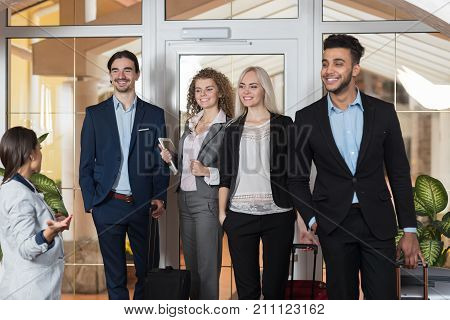 Hotel Administrator Welcome Business People In Lobby, Mix Race Businesspeople Group Guests Arrive Entrance With Suitcase