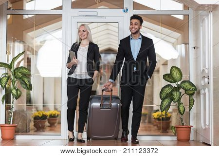 Business Couple In Hotel Lobby, Businesspeople Group Man And Woman Guests Arrive Entrance With Suitcase