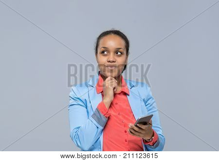 Young Business Woman Using Cell Smart Phone African American Girl Looking To Copy Space Businesswoman Isolated Over Gray Background