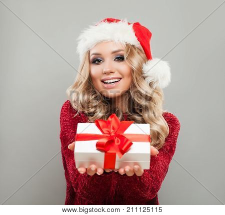 Christmas Woman in Santa Hat Holding White Xmas Gift Box with Red Ribbon. Happy Model with Blonde Hair Makeup and Christmas Gift. New Year or Christmas Concept