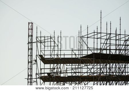 upper end silhouette of scaffolding, building construction, profile sunset light structure of scaffolding and cranes