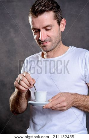 young dark haired man in white shirt drinking espresso