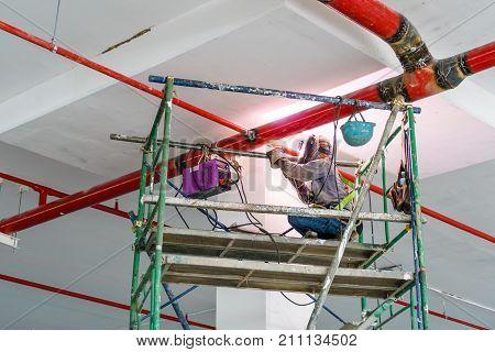 Welder man welding the steel red pipe on the scaffold. An electric welder works on scaffolding.