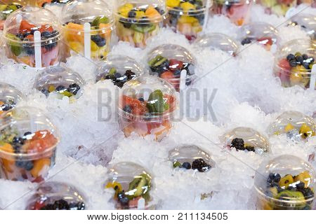 Fresh fruit in plastic cups on a showcase with ice.
