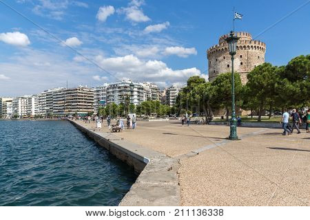 THESSALONIKI, GREECE - SEPTEMBER 30, 2017:  People walk down in front of White Tower in city of Thessaloniki, Central Macedonia, Greece