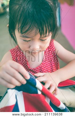 Closeup of adorable asian girl packing stuff in backpack at home. Asian child preparing for first day at school. Do it yourself concept. Shallow depth of field (dof). Vintage film filter effect.