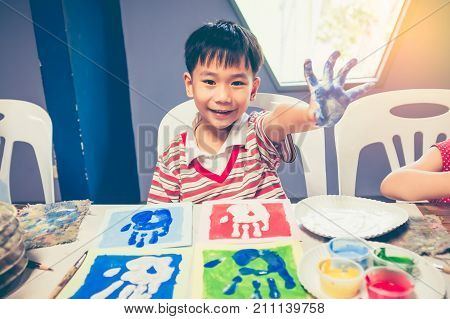 Handsome asian boy smiling and showing hands in paint. Pop art style imprint of a kids hand on art class. Strengthen the imagination of child for learning and education concepts. Vintage effect tone.