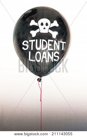 Black balloon with the words 'student loanst' representing the economic financial consumer student and auto loan debt bubble.