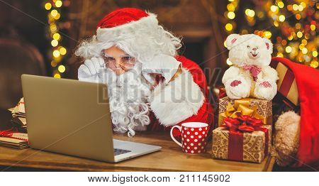 Santa Claus with a computer before christmas