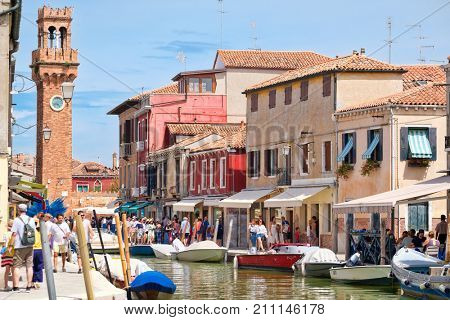 VENICE,ITALY - JULY 27,2017 : Clocktower, colorful houses and canal, a typical scene at the island of Murano