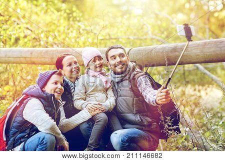 travel, tourism, hike and technoligy concept - happy family with backpacks taking picture by smartphone and selfie stick in woods