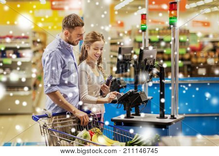 shopping, sale, payment, consumerism and people concept - happy couple with bank card buying food at grocery store or supermarket self-checkout cash register over snow