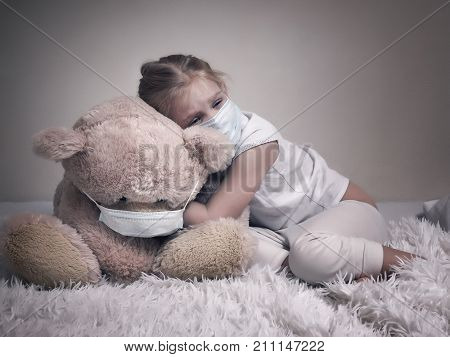 Little girl and big plush bear in medical masks. The concept of childhood diseases empathy support and help sick children poster