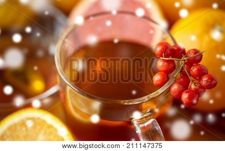 health, traditional medicine, folk remedy and ethnoscience concept - close up of tea cup with rowanberry over snow