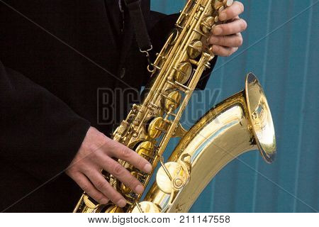Close Up Of Street Saxophone Player Hands Playing Alto Sax Musical Instrument Over Blue Background ,