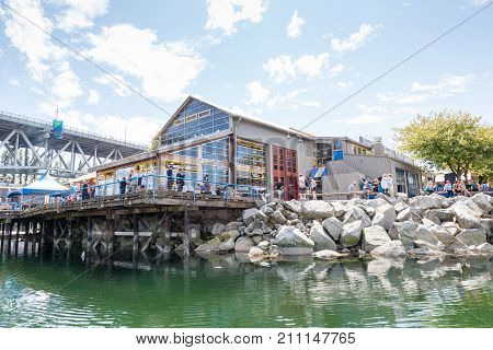 VANCOUVER CANADA - AUG. 16 2017: Visitors resting at the Granville Island Public Market. Granville Island is located across False Creek from downtown Vancouver.