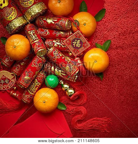 Chinese coins of luck and chinese firecrackers or chinese knot and Chinese gold ingots and Traditional chinese knot (Foreign text means blessing) and Red envelopes and decoration with Fresh oranges on Red Paper background poster