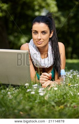 Beautiful woman browsing internet in citypark, laying in grass, looking at camera.?