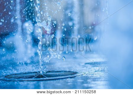 The gush of water of a fountain. Splash of water in the fountain, abstract image. bokeh of blue water