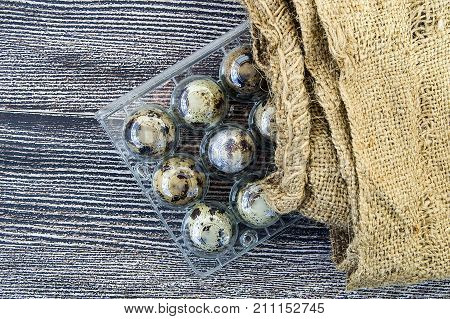 quail eggs in a plastic box,many quail eggs on a wooden floor,