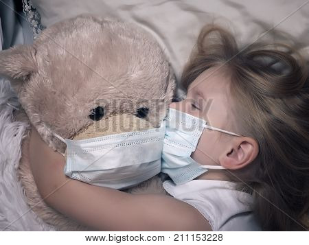 Little girl and big plush bear sleep in medical masks. The concept of childhood diseases empathy support and help sick children